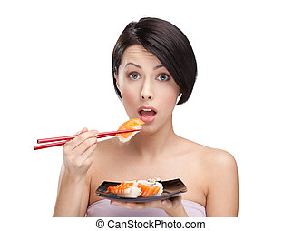 Surprised young woman holding sushi with a chopsticks, ...