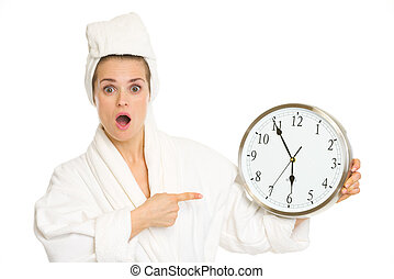 Surprised young woman in bathrobe pointing on clock