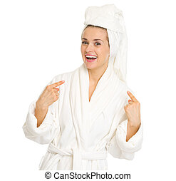 Surprised young woman in bathrobe pointing on herself