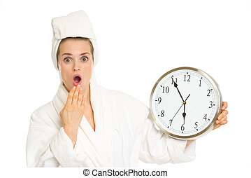 Surprised young woman in bathrobe with clock