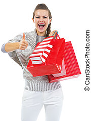 Surprised young woman in sweater with shopping bags showing thumb