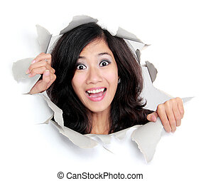 surprised young woman looking through a hole
