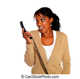 Surprised young woman looking to phone