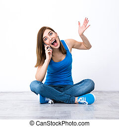 Surprised young woman sitting on the floor and talking on the phone