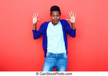 Surprised young woman standing with her hands raised