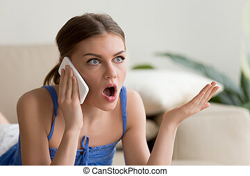 Surprised young woman talking on mobile phone, confused...