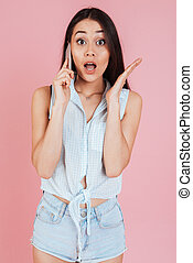 Surprised young woman talking on the phone