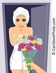 Surprised young woman wrapped in white towel receiving bouquet of flowers from men's hand next to open door