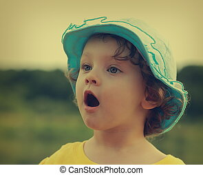 Surprising fun child with opened mouth looking outdoors ...