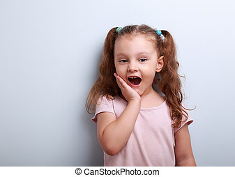 Surprising fun girl looking with open mouth on blue background