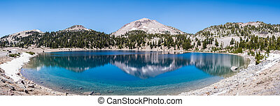 Surrounding mountains reflected in the calm waters of Lake ...