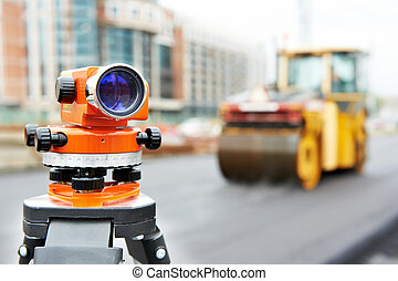 Construction surveyor equipment automatic level tool during asphalt paving works with compactor roller at background