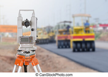 Survey equipment theodolite on a tripod. with road under...