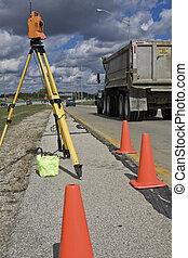 Survey on the highway - orange theodolite and semi-truck.