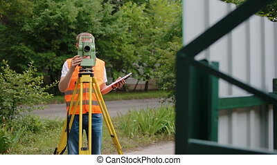 Surveyor at work measuring the distance. One caucasian man...