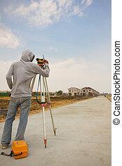Surveyor engineer making measure on the road