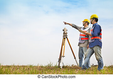 Surveyor engineer making measure with partner on the field