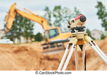 Surveyor equipment level outdoors at construction site - ...