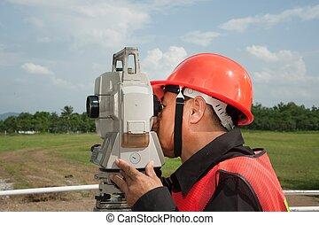 Surveyor or Engineer making measure on the field.
