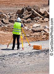Surveyor taking measurements at a construction site