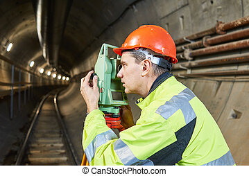 Surveyor with theodolite level at underground railway tunnel...