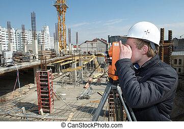 Surveyor with transit level equipment - worker surveyor...