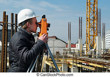 Surveyor with transit level equipment - worker surveyor...