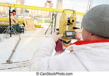 surveyor worker and theodolite at construction site