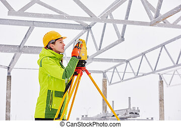surveyor works with theodolite - female surveyor worker...