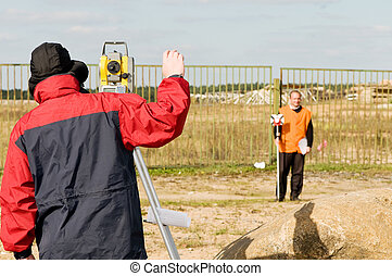 surveyor works with theodolite - Two surveyor workers with ...