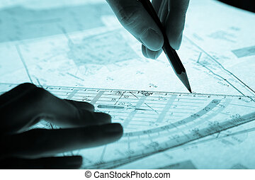 surveyor\'s plan and hands with a pencil