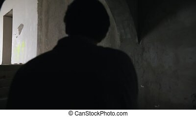 Survived man walking in the dark in abandoned building with...