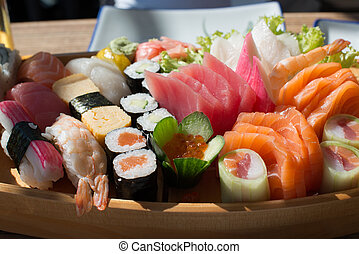 Japanese cuisine: prepared and delicious sushi and sashimi closeup on wooden tray