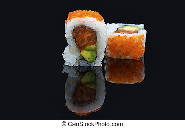 Sushi arranged on a shiny black surface looking delicious