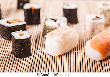 an assortment of different sushi pieces on a wooden bamboo sushi mat in a japanese restaurant