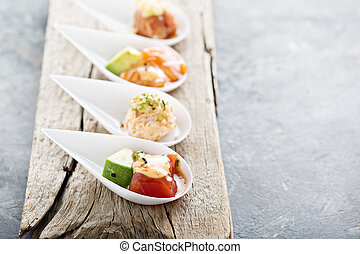 Sushi bite sized appetizers with raw salmon and tuna, asian cuisine concept