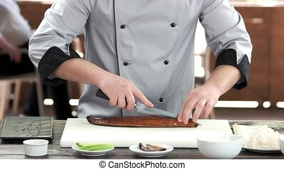 Sushi chef cutting smoked eel. Man preparing food, fish.