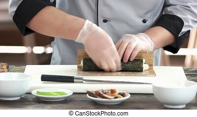 Sushi chef using bamboo mat. Japanese food preparation in...