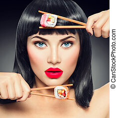 Sushi. Fashion art portrait of beauty model girl eating sushi rolls