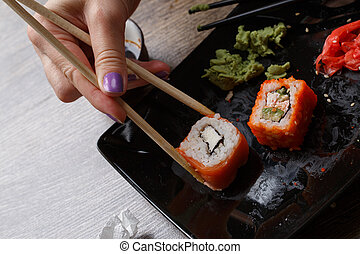 Sushi. Hand with chopsticks