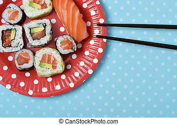 sushi in a red plate patterned with white dots