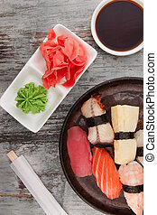 Sushi in a round plate over wooden background