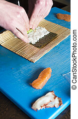 Sushi in sushi bar. Sushi making. Hands rolling sushi