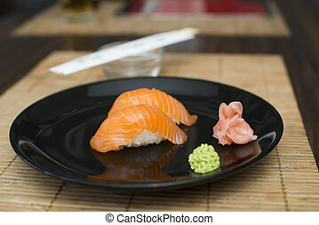 Sushi in sushi bar. Table and ration sushi with salmon