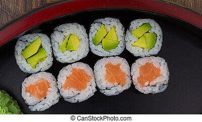 Sushi maki in a black plate