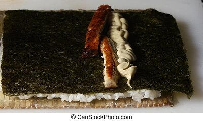 Sushi master puts a filling on a nori. Close up