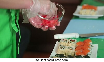 Sushi master puts ginger on a pot with sushi