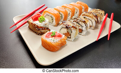 sushi on a plate with a black background