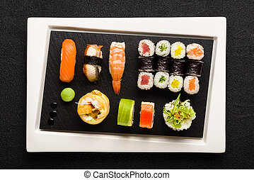Sushi on white plate with black stone surface