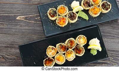 Sushi on wooden background. Delicious breaded maki rolls.
